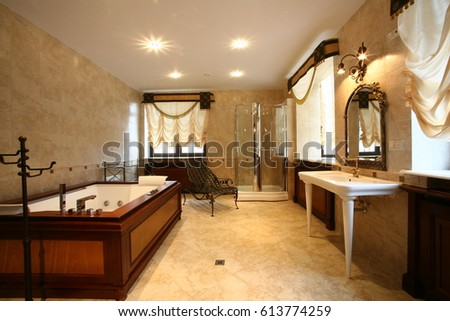 Spacious light bathroom in classic style with marble floor and walls, with luxurious white plumbing, jacuzzi