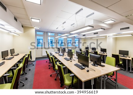 Spacious, light classroom with long, wood desk, green chairs and computers - stock photo