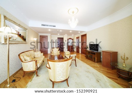 Spacious living room with carved armchairs, sofa, table and TV in classic style.