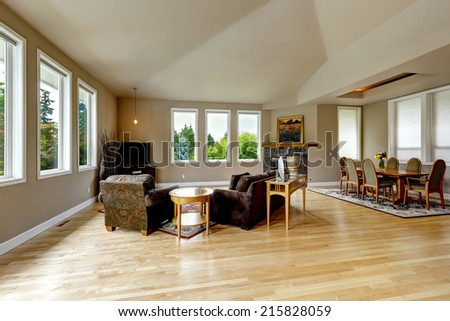 Spacious living room with high vaulted ceiling and hardwood floor. Granite background fireplace, elegant dining table set