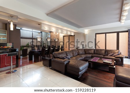 Spacious living room with huge sofa in a luxury house - stock photo