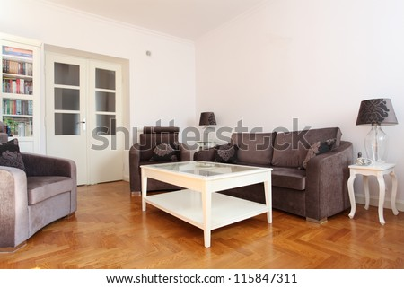 Spacious living room with wooden floor and bright walls - stock photo