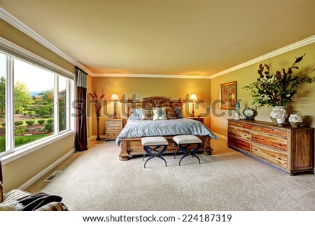 Spacious luxury bedroom with carved wood bed, nightstands and dresser decorated with flowers - stock photo