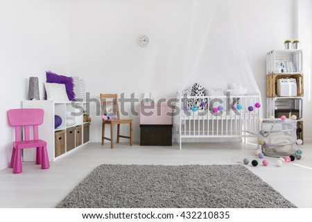 Spacious modern baby's room with soft grey carpet in the middle and white cradle by the wall