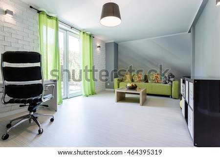 Spacious modern interior with office chair, brick wall, sofa and small table
