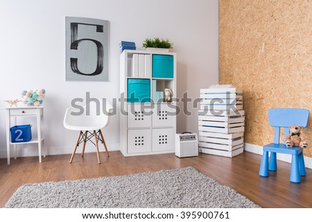 Spacious modern room for boy. In the corner boxes with toys and shelf with books - stock photo