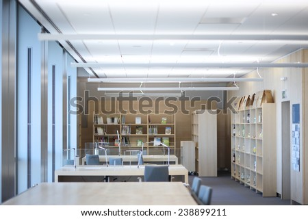 Spacious reading-room interior, rows of free tables - stock photo