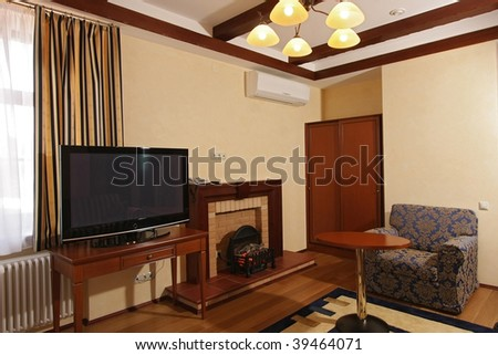 Spacious room with armchairs, a window and the TV