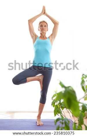 Spacious view of a mature healthy sporty woman using a yoga mat to exercise and stretch her body in a light and airy interior. Fit professional woman balancing in a yoga position, indoors. - stock photo