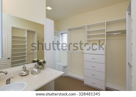 Spacious Walk in Closet with sink and mirror. Large white walk-in closet with shelves. - stock photo