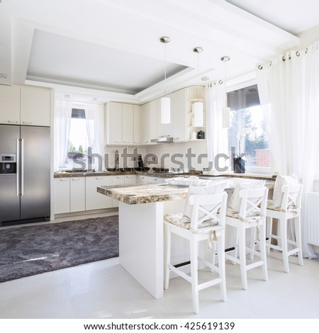 Spacious,white kitchen with counter-top dining place - stock photo