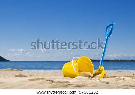 Spade and bucket by the water's edge, ready to build a sandcastle. - stock photo