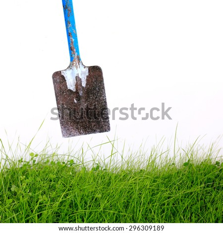 Spade and grass isolated on white background