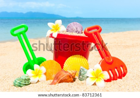 Spade and other toys on tropical beach island - stock photo