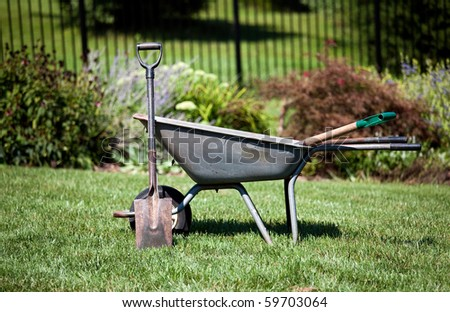 Spade resting against a wheelbarrow in a flower filled back garden - stock photo