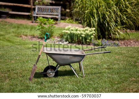 Spade resting against a wheelbarrow in a flower filled back garden with seat in background
