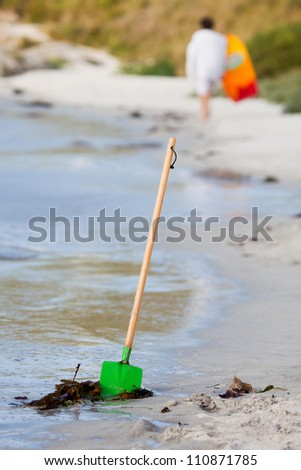 spade sticks in the sand of a beach with a walking girl at the blurred background