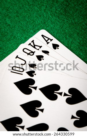 spades straight flush poker cards on green table - stock photo