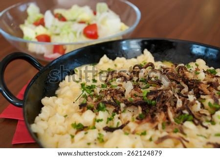 spaetzle with melted cheese in pan - käsespätzle kasnocken - stock photo