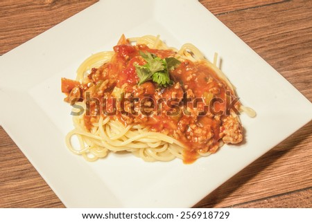 Spagett bolognaise and few coriander leafs, on a white plate