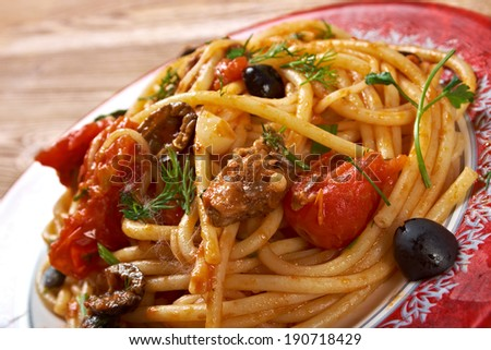 Spaghetti alla puttanesca  salty Italian pasta dish.ingredients are typical of Southern Italian cuisine: tomatoes, olive oil, olives, capers and garlic. - stock photo