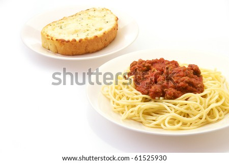 Spaghetti and garlic bread on a white background with copy space - stock photo