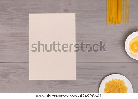 spaghetti and macaroni cooking concept - close up of pasta on wooden gray table with ingredients and paper. Top view on food - stock photo