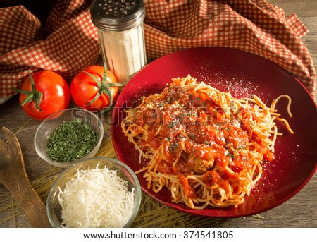 Spaghetti And Meatball Dinner. Parmesan cheese, oregano, paprika, and mozzarella cheese surround a plate of spaghetti and meatballs with a red and white gingham background. - stock photo