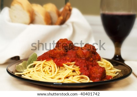 Spaghetti and meatballs dinner with red wine, garlic bread, and breadsticks. - stock photo