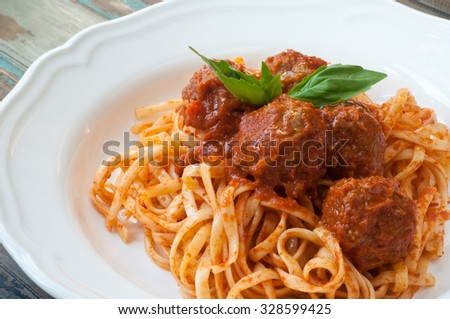 Spaghetti and meatballs in a tomato and herb sauce topped with fresh basil. A traditional italian pasta dish served in a white bowl on a rustic wooden table. - stock photo