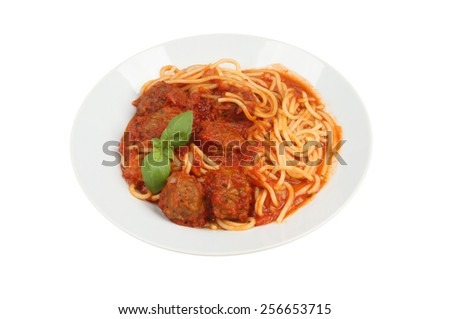 Spaghetti and meatballs with a sprig of basil in a bowl isolated against white - stock photo