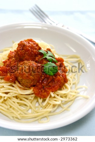 Spaghetti and meatballs with rich tomato sauce, garnish with herbs.