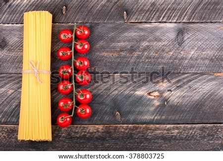 Spaghetti and tomatoes on old rustic background. Pasta background. Ingredients for cooking pasta. Top view - stock photo