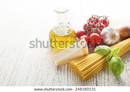 Spaghetti and tomatoes with parmesan cheese on a vintage wooden table - stock photo