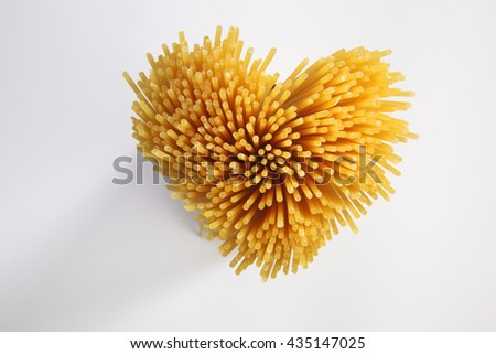 spaghetti arranged in a heart shape  - stock photo