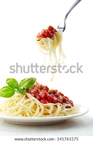 Spaghetti bolognese and green basil leaf on white plate - stock photo