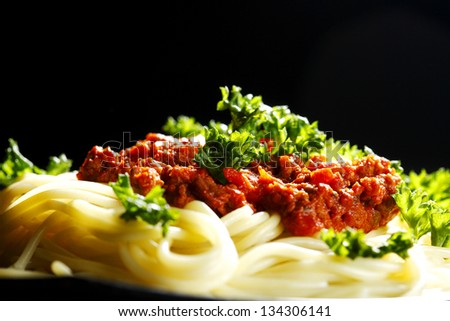 Spaghetti bolognese in black plate on dark background - stock photo