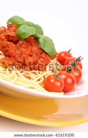Spaghetti Bolognese on a plate decorated with fresh basil and cherry tomatoes in close up
