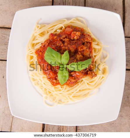 Spaghetti bolognese on a plate on a wooden background - stock photo