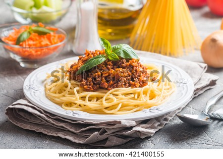 Spaghetti bolognese on white plate with ingredients on gray background - stock photo