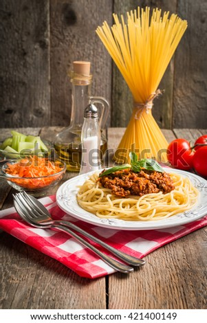 Spaghetti bolognese on white plate with ingredients on wooden background - stock photo