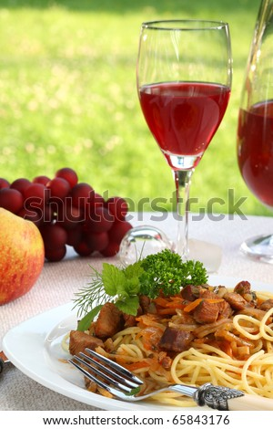 Spaghetti bolognese, wine and fruits on a dinner table.