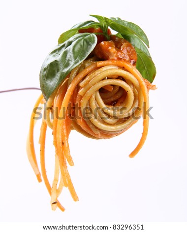 Spaghetti bolognese with basil leaves on a fork - stock photo