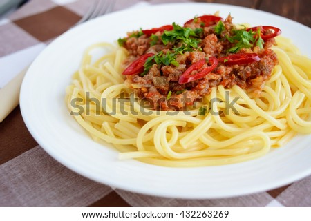 Spaghetti Bolognese with chili on a white plate on a wooden background. Close up