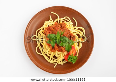 Spaghetti Bolognese with fresh herb spices - oregano, basil, rosemary, celery and red pepper, served on rustic, brown ceramic plate over white background - stock photo