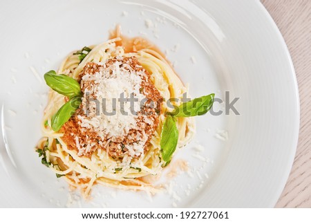 Spaghetti Bolognese with parmesan cheese and basil twig