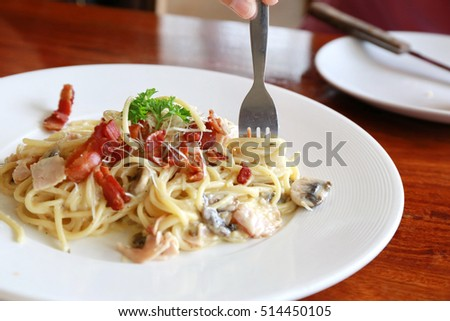 spaghetti carbonara ,hand use fork rolling spaghetti for eating.