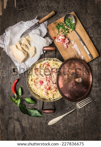 Spaghetti carbonara in copper pan with parmesan, and herbs on cutting Board , top view - stock photo