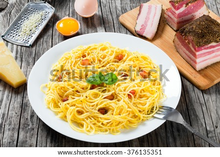 Spaghetti carbonara on a white dish, authentic Italian recipe with egg yolks, grated parmesan cheese and bacon, freshly ground black pepper, decorated basil leaves, close-up, top view - stock photo