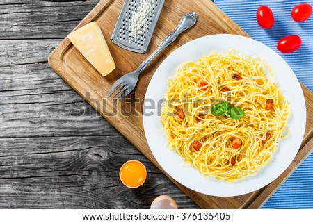 Spaghetti carbonara on a white dish with basil leaves, egg yolks, grated parmesan cheese, bacon, freshly ground black pepper, traditional Italian recipe, top view - stock photo